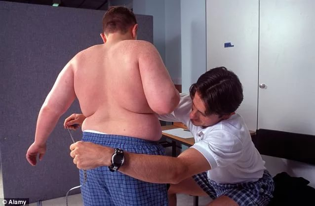 man measures the waist of fat boy